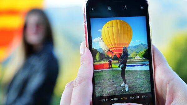 Девушка фотографируется на Фестивале воздушных шаров Солохаул парка в Сочи