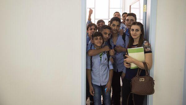 Школьники с учительницей в классе открывшейся в районе Барза в Дамаске школы, отремонтированной на собранные в России средства