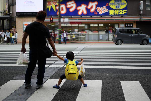 Мужчина c ребенком на пешеходном переходе в центре Оиты, Япония