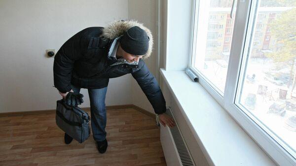 Мужчина проверяет отопление в квартире