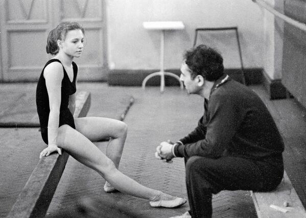 Тренер Владимир Рейсон  беседует с гимнасткой Натальей Кучинской на тренировке.