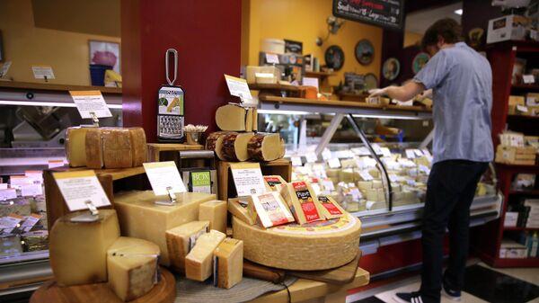 Покупатель в отделе импортного сыра в супермаркете в Сан-Франциско, США