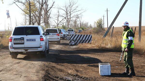 Автомобили наблюдателей ОБСЕ на пропускном пункте в селе Петровское, где должен состояться отвод сил бойцов подразделений ДНР