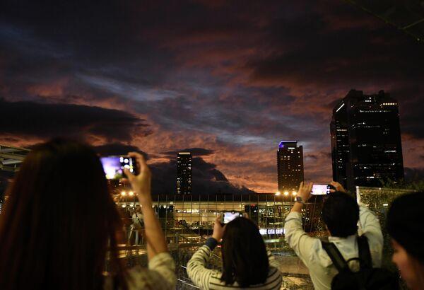 Люди фотографируют закат в Осаке, Япония. 12 октября 2019