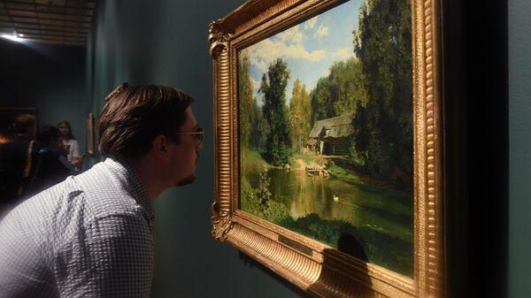 Посетитель рассматривает картину Василия Поленова Пруд в Абрамцеве в Третьяковской галерее на Крымском валу
