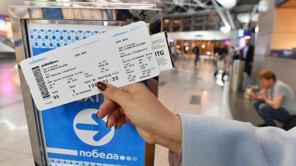 Пассажир демонстрирует авиабилеты авиакомпании Победа
