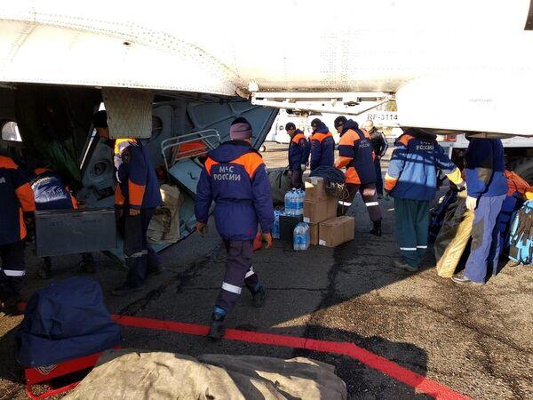 Сотрудники аварийно-спасательной службы МЧС РФ производят загрузку вертолета всем необходимым для дальнейшей высадки на месте прорыва технологической дамбы в Курагинском районе Красноярского края