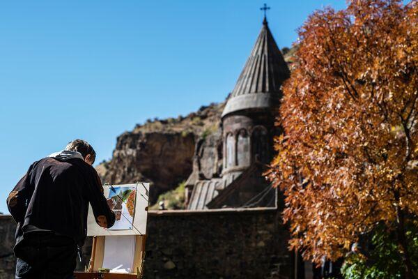 Молодой человек рисует монастырь Гегард в Котайкской области Армении