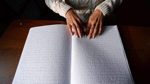 Незрячая женщина читает с помощью рук книгу, в которой использован шрифт Брайля