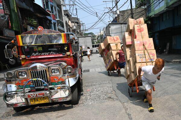 Рабочие с тележками на улице в китайском квартале Манилы