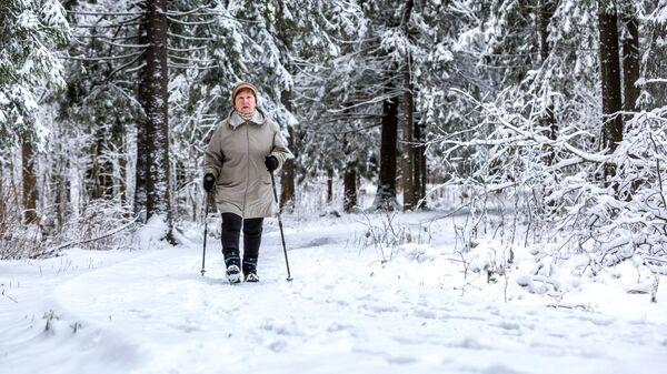 Женщина занимается скандинавской ходьбой
