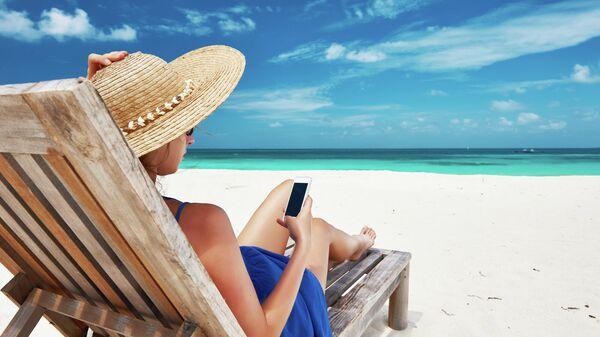 Девушка с телефоном на пляже