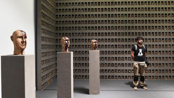 Художник Андрей Кузькин рядом со своей работой Молельщики и герои в экспозиции VIII Московской международной биеннале современного искусства