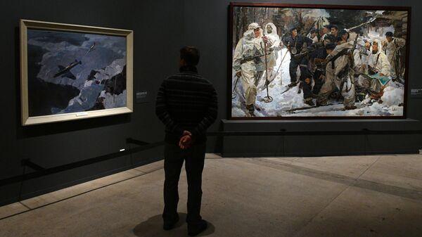 Посетитель у картины Иосифа Серебряного Партизанский отряд на выставке Память поколений: Великая Отечественная война в изобразительном искусстве