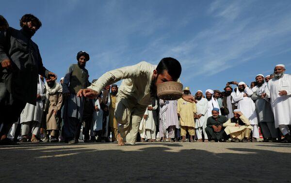 Сторонник политической и религиозной партии JUI-F во время участия в традиционной игре Шляпа в Исламабаде, Пакистан