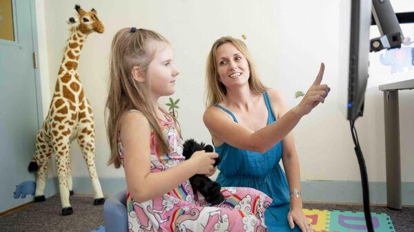 Джессика Кантлон и ребенок работают над математической игрой