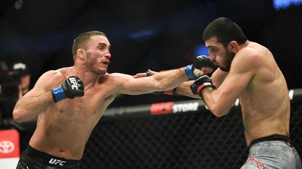 Рамазан Эмеев (Россия) и Энтони Рокко Мартин (США) (слева) во время боя в полусреднем весе на турнире по смешанным единоборствам UFC Fight Night в Москве.