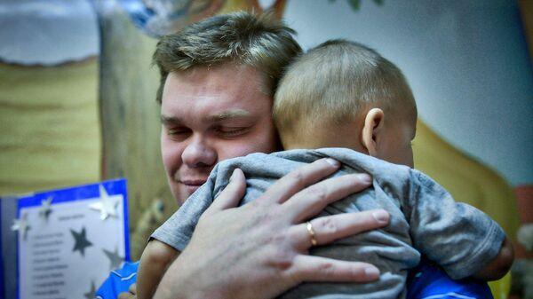 Приемный отец обнимает ребенка