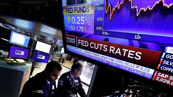 Экран на Нью-Йоркской фондовой бирже с новостью о снижении базовой процентной ставки, 30 октября 2019 года