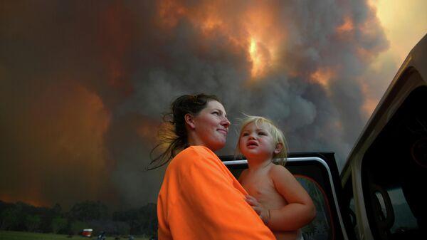 Женщина с дочерью смотрят на дым от лесных пожаров, Австралия, 12 ноября 2019 года