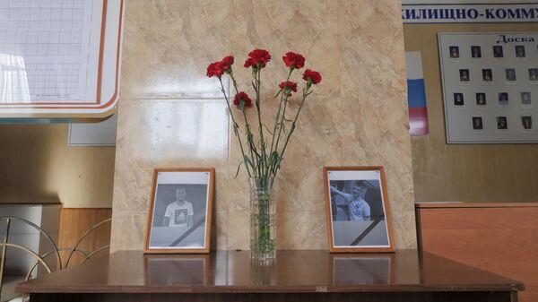 Цветы у портретов погибших молодых людей в холле Амурского колледжа строительства и жилищно-коммунального хозяйства в Благовещенске, где произошла стрельба