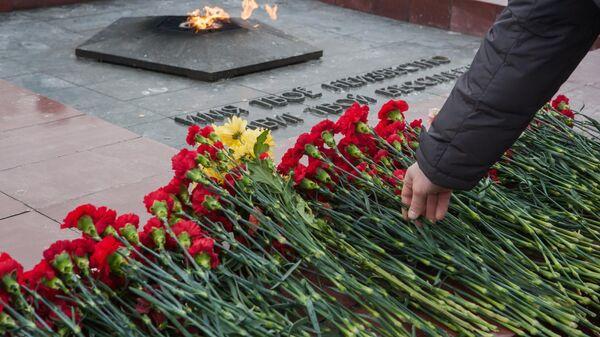 Люди возлагают цветы к Мемориальному комплексу
