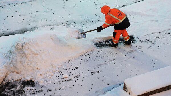 Сотрудник коммунальной службы убирает снег