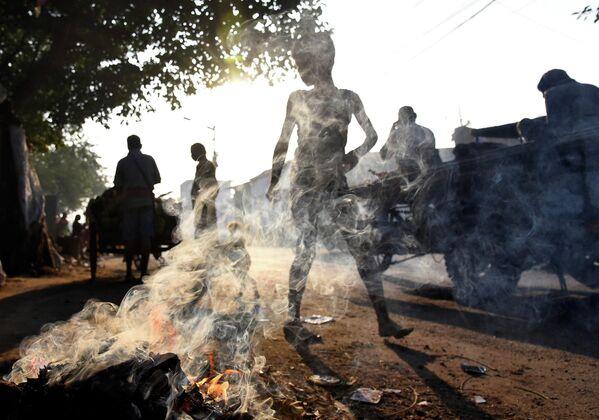 Люди проходят мимо горящего мусора в Калькутте, Индия