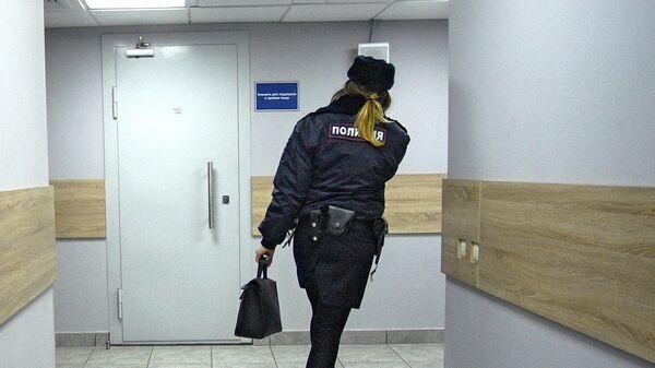 Сотрудница  полиции идет по коридору дежурной части