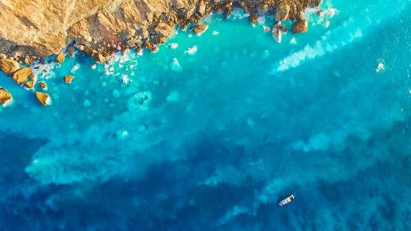 Вид с воздуха на горячие источники у побережья вулканического острова Гуйшань