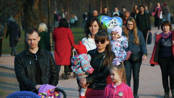 Молодая семья с детьми во время прогулки в парке