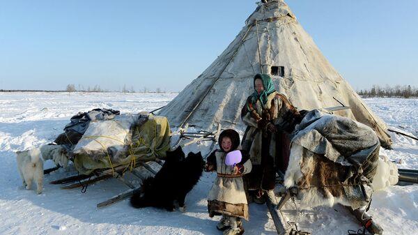 Женщина с ребенком у чума в стойбище в Надымском районе Ямало-Ненецкого автономного округа