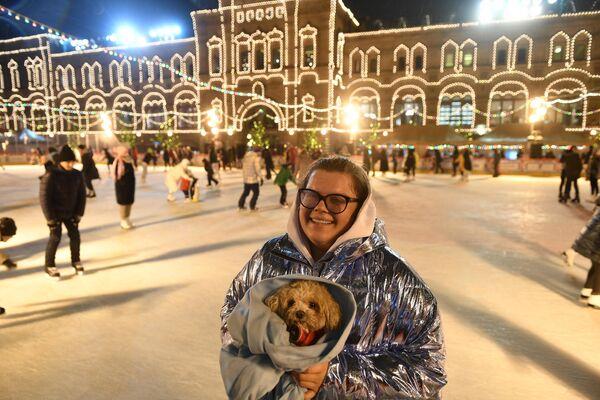 Посетительница вместе с собакой на открытии ГУМ-катка на Красной площади