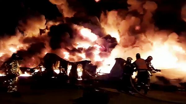 Сотрудники МЧС России тушат пожар в ангаре на территории промышленной зоны в Санкт-Петербурге. Стоп-кадр с видео, предоставленного МЧС