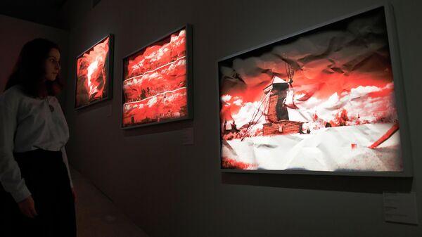 Посетительница выставки работ фотографа Арсена Ревазова Невидимый свет в Третьяковской галерее