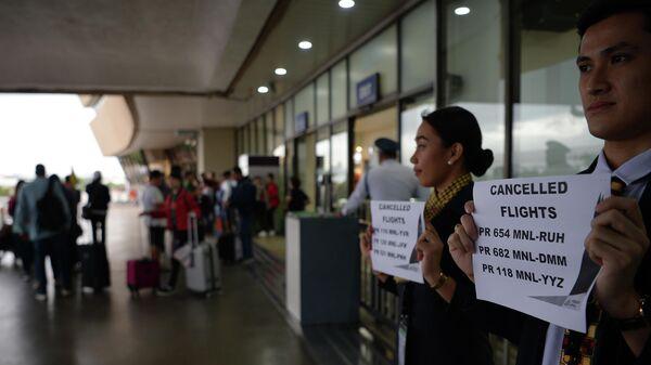 Сотрудники авиакомпании держат таблички с номерами отмененных рейсов в аэропорту Манилы, Филиппины. 3 декабря 2019