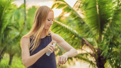 Девушка распыляет средство против насекомых