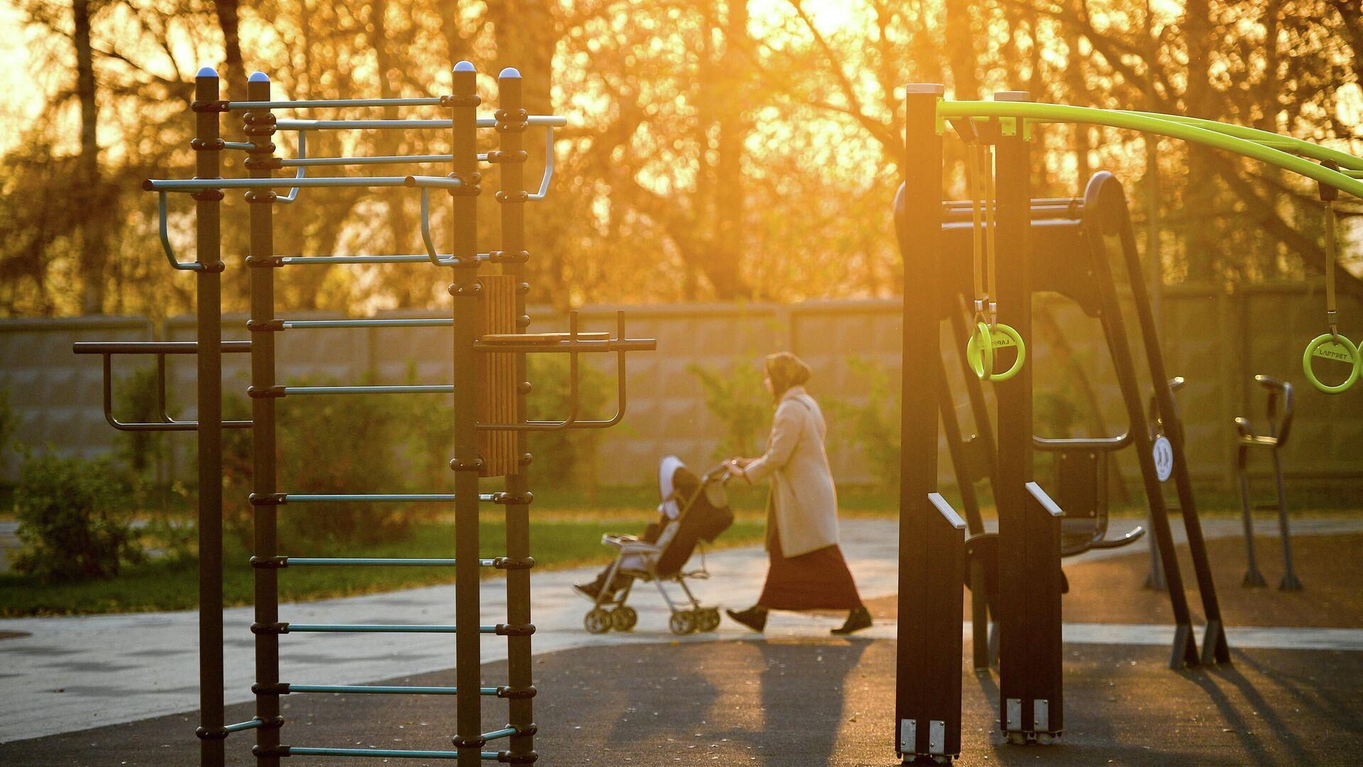 Женщина с ребенком проходит мимо спортивной площадки - РИА Новости, 1920, 09.09.2020