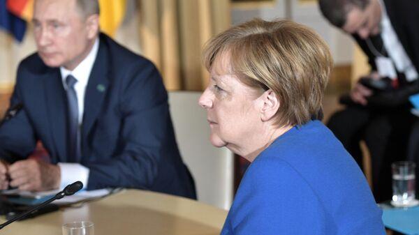 Президент РФ Владимир Путин и  федеральный канцлер Германии Ангела Меркель во время встречи в Нормандском формате в Елисейском дворце