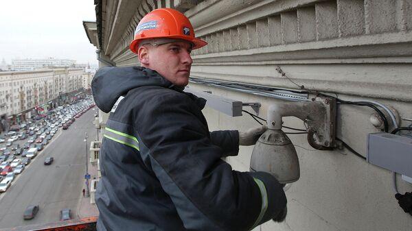 Рабочий производит монтажные работы по установке художественной подсветки на здание