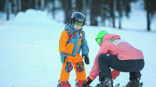 Инструктор учит ребенка кататься на горных лыжах в ГЛК Манжерок