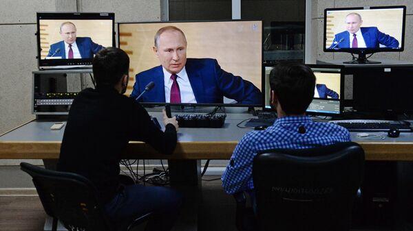 Сотрудники телеканала Грозный смотрят трансляцию пресс-конференции президента РФ Владимира Путина