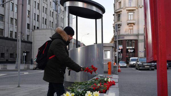 Молодой человек оставляет цветы у площади Воровского на пересечении улиц Кузнецкий мост и Большая Лубянка