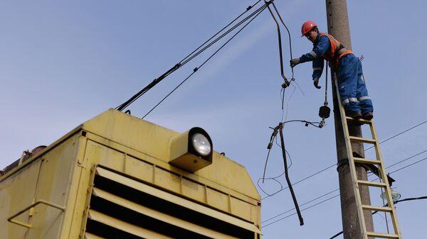 Рабочий восстанавливает электрические линии