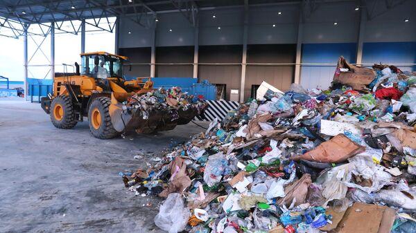Экскаватор-погрузчик на территории комплекса по переработке отходов Восток в Московской области