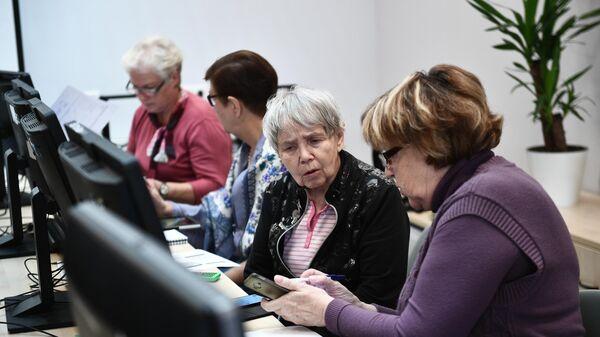Пенсионеры во время обучения работы на компьютере