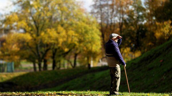 Пожилой мужчина на прогулке в парке