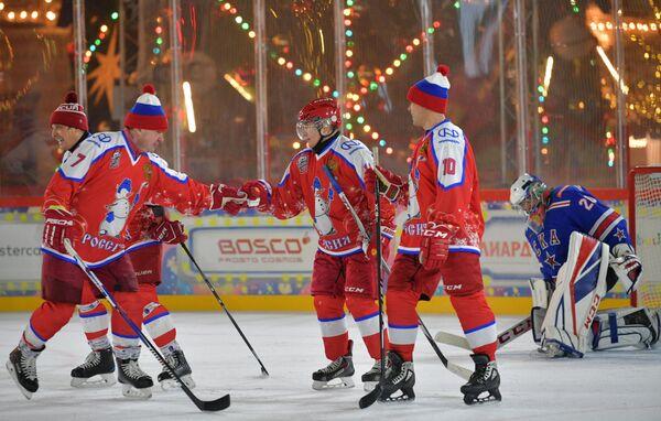 Президент РФ Владимир Путин радуется заброшенной шайбе в предновогоднем товарищеском матче Ночной хоккейной лиги на катке на Красной площади