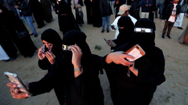 Саудовские женщины в специальных защитных очках смотрят кольцевое солнечное затмение на Джабаль-Арбе в Хофуфе. 26 декабря 2019 года