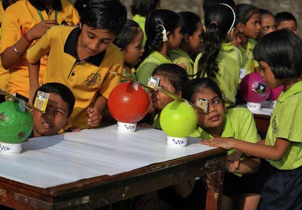 Дети используют камеры-обскуры для наблюдения кольцевого солнечного затмения в Мумбаи, Индия